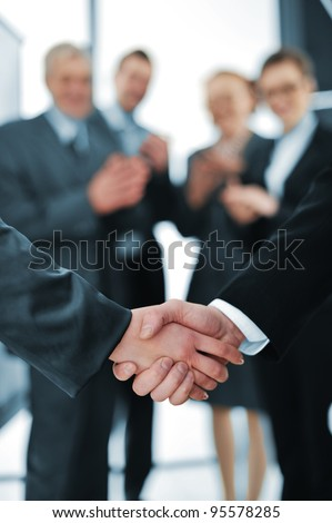 Succesful handshake with business people aplauding