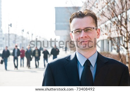 Succesful young man with group of people in the background - stock photo