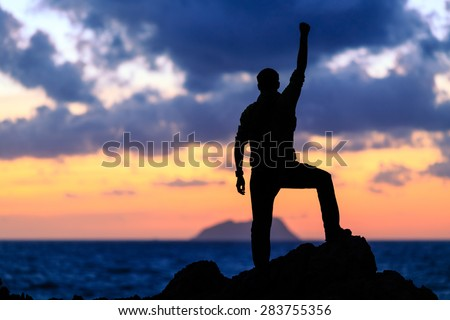 Success achievement running or hiking accomplishment business and motivation concept with man sunset silhouette celebrating arms up raised outstretched trekking climbing running outdoors in nature - stock photo