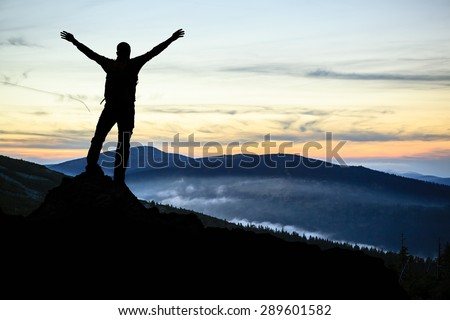 Success and achievement, accomplish hiking man silhouette concept with climber with arms up, outstretched on mountains peak, healthy lifestyle at sunset