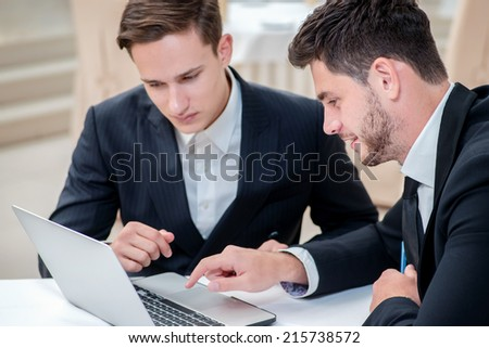 Success and confidence. Two successful and confident businessman sitting at the table in a business office in full costume in the office and working at a laptop - stock photo