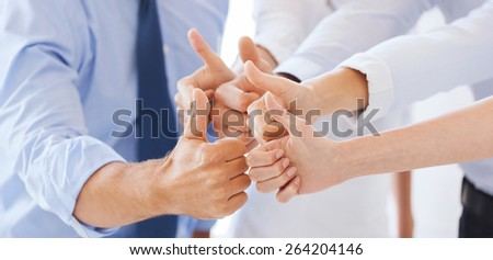 success and winning concept - happy business team showing thumbs up in office - stock photo