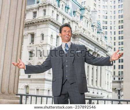 Success Businessman. Dressing in dark blue three piece suit, necktie, a handsome, sexy, middle age businessman is standing outside office building, stretching two arms, laughing. - stock photo