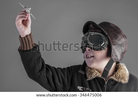 success, child playing the aircraft pilot with hat and retro bomber jacket - stock photo