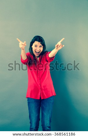 success concept - fun 30s woman shouting with extrovert hand gesture to express excitement or joy,studio shot, blue effects