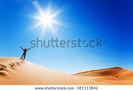 Success concept: rear view of a adult white man standing on a sand dune and holding arms up. Erg Chebbi, Morocco. - stock photo