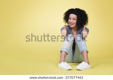 Success concept with woman: Successful happy woman with thumbs up being excited on isolated yellow background with empty copy space. - stock photo