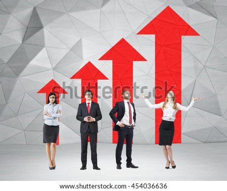 Success concept with young businesspeople and red arrow chart in room with polygon patterned concrete wall - stock photo