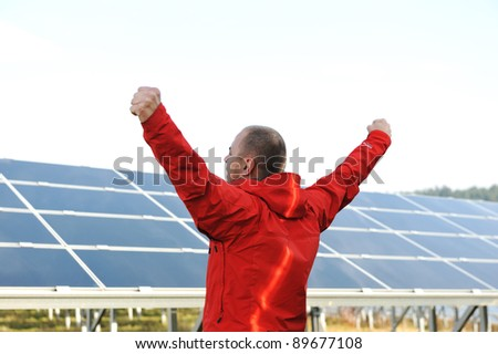 Success, engineer in solar panel fields opening arms up - stock photo