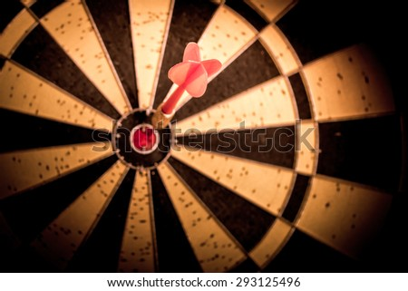 Success hitting target aim goal achievement. Red dart in target center on dartboard, vintage effect filter - stock photo