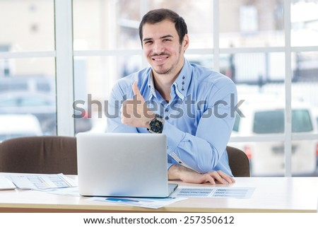 Success in business. Successful businessman working at his laptop and showing thumb up while handsome young man sitting in the office at the table. - stock photo