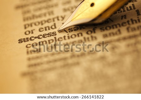 Success pen nib pointing to the words in the dictionary, shot with very shallow depth of field, - stock photo