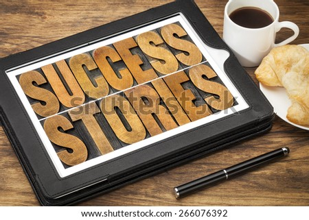 success stories typography - word abstract in vintage letterpress wood type on a digital tablet with a cup of coffee - stock photo