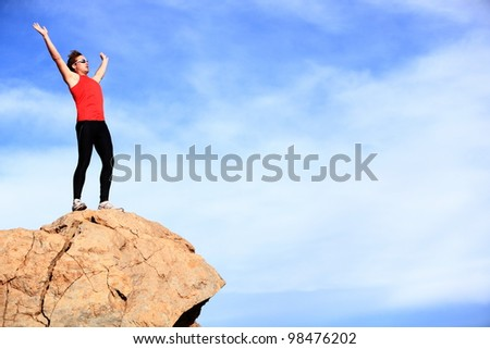 Success - winner reaching summit. Athlete in fitness sport clothes and running shoes reaching the goal cheering with arms raised. Man fitness model happy with lots of copyspace on blue sky.