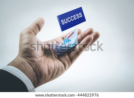 Success word on flag with boat made of paper graph in businessman hand.For business financial concept.