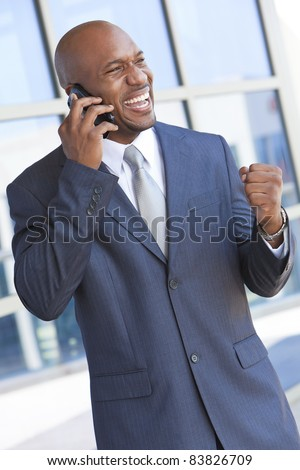Successful African American businessman or man in a suit in a modern city talking on his cell phone - stock photo