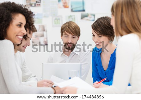 Successful African American businesswoman smiling as she sits in a meeting with her coworkers as they have a brainstorming session - stock photo