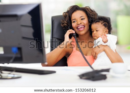 successful african businesswoman talking on landline phone while holding her little baby girl - stock photo