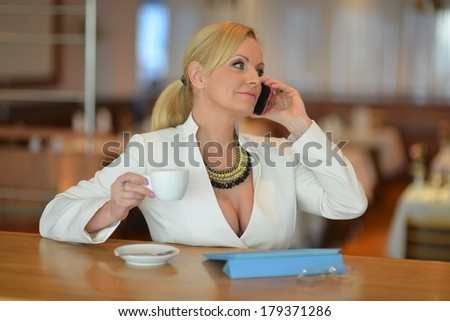 Successful and attractive middle aged woman chatting on the phone during her lunch break   - stock photo