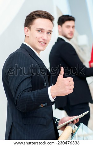 Successful and confident businessman. Young businessman standing on the steps and keeps the tablet and a thumbs-up while his colleagues talk and shake hands with each other - stock photo