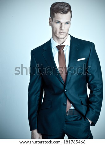 Successful and confident young businessman on light-blue background - stock photo