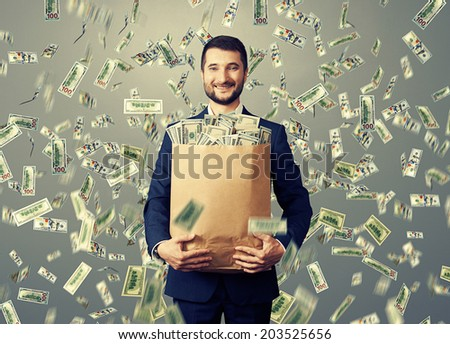 successful and smiley businessman holding paper bag with money under dollar's rain - stock photo