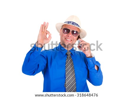 Successful and smiling businessman in jeans, blue shirt, tie, sunglasses and white hat. Speaking by cell mobile phone and shows gesture OK. Isolated white background, Concept of leadership and success - stock photo