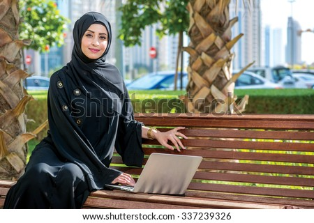 Successful Arab woman and laptop. Arab businesswoman wearing hijab working on a laptop in the park on the background of skyscrapers of Dubai. The woman is dressed in a black abaya - stock photo