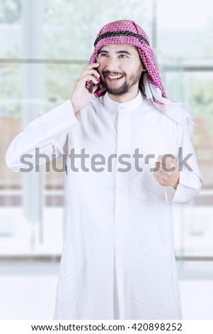 Successful Arabian businessman standing in the office while speaking on the cellphone and expressing his success