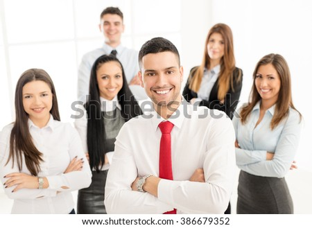 Successful arabian businessman with crossed arms standing proudly in front his young business team and looking at the camera.