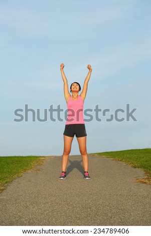 Successful asian athlete raising arms for celebrating running work out goals. - stock photo