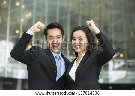 Successful Asian business team with arms up celebrating. Excited Chinese business people celebrating. Business concept. - stock photo