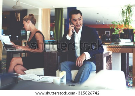 Successful asian man entrepreneur speaking on cell phone, beautiful woman studying documents with reports while work on laptop computer, business people preparing for briefing in office space interior - stock photo