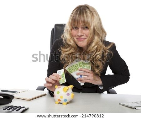 Successful attractive young blond entrepreneur saving her money from the profits of her business placing a 100 euro banknote into a piggy bank - stock photo