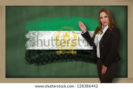 Successful, beautiful and confident woman showing flag of afghanistan on blackboard for marketing research, presentation and tourist advertising - stock photo