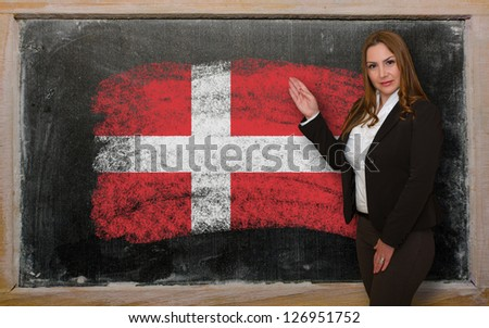 Successful, beautiful and confident woman showing flag of Denmark on blackboard for marketing research, presentation and tourist advertising