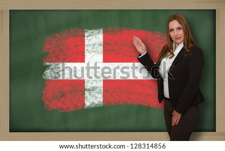 Successful, beautiful and confident woman showing flag of denmark on blackboard for marketing research, presentation and tourist advertising - stock photo