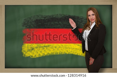 Successful, beautiful and confident woman showing flag of germany on blackboard for marketing research, presentation and tourist advertising - stock photo