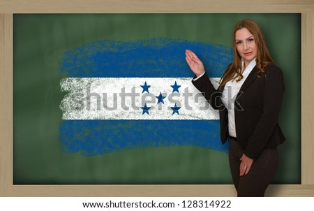 Successful, beautiful and confident woman showing flag of honduras on blackboard for marketing research, presentation and tourist advertising - stock photo
