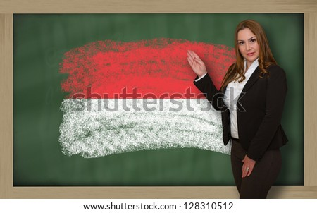 Successful, beautiful and confident woman showing flag of indonesia on blackboard for marketing research, presentation and tourist advertising - stock photo
