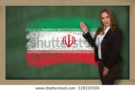 Successful, beautiful and confident woman showing flag of iran on blackboard for marketing research, presentation and tourist advertising - stock photo