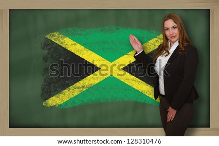 Successful, beautiful and confident woman showing flag of jamaica on blackboard for marketing research, presentation and tourist advertising - stock photo