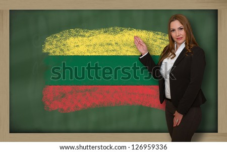 Successful, beautiful and confident woman showing flag of lithuania on blackboard for marketing research, presentation and tourist advertising - stock photo
