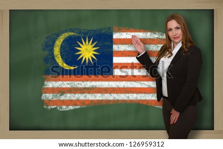 Successful, beautiful and confident woman showing flag of malaysia on blackboard for marketing research, presentation and tourist advertising - stock photo