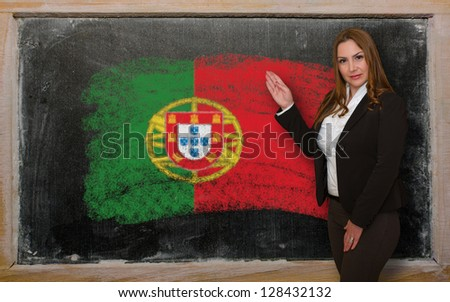 Successful, beautiful and confident woman showing flag of Portugal on blackboard for marketing research, presentation and tourist advertising