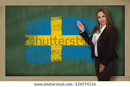 Successful, beautiful and confident woman showing flag of sweden on blackboard for marketing research, presentation and tourist advertising - stock photo