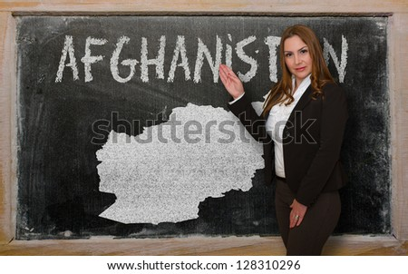 Successful, beautiful and confident young woman showing map of afghanistan on blackboard for presentation, marketing research and tourist advertising - stock photo