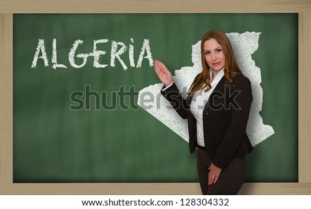 Successful, beautiful and confident young woman showing map of algeria on blackboard for presentation, marketing research and tourist advertising - stock photo