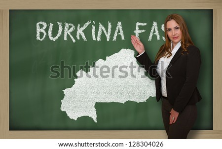 Successful, beautiful and confident young woman showing map of burkina faso on blackboard for presentation, marketing research and tourist advertising - stock photo