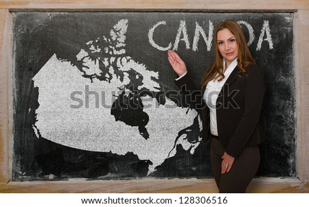 Successful, beautiful and confident young woman showing map of canada on blackboard for presentation, marketing research and tourist advertising - stock photo